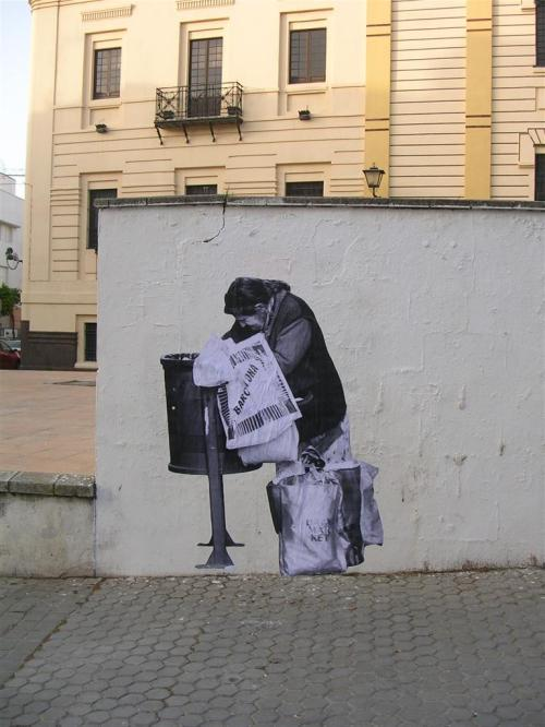 Señora buscando en una papelera de la calle. Grafiti 61