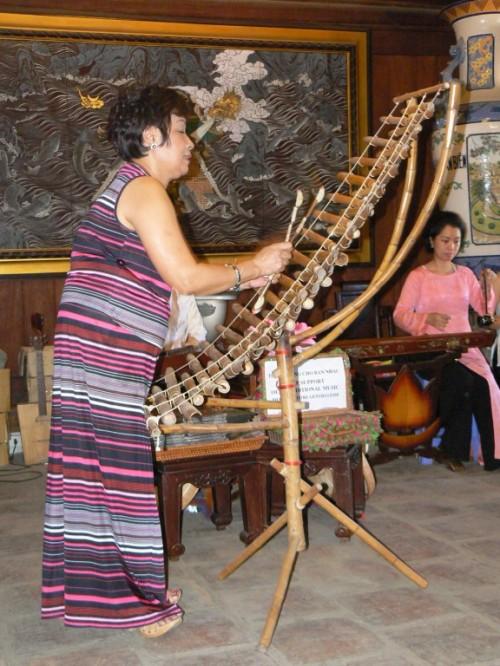 """Foto de mujer tocando el T'rung """"xilofono de bambu"""" en el Templo de la Literatura en Hanoi - Vietnam. Foto por martin_javier"""